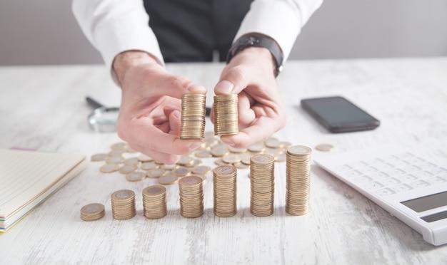 Uomo d'affari che mostra le monete sulla scrivania.