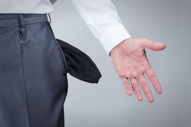 Uomo d'affari che mostra le tasche vuote