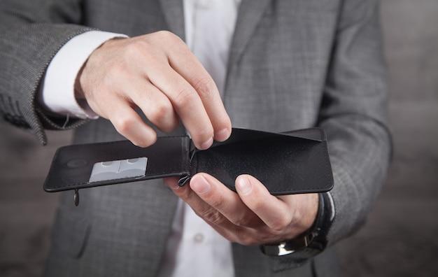 Uomo d'affari che mostra portafoglio vuoto. fallimento
