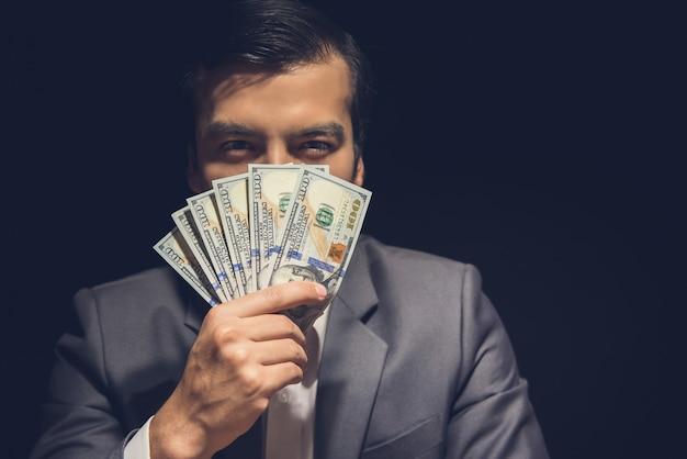 Uomo d'affari che mostra i guadagni finanziari in dollari americani.