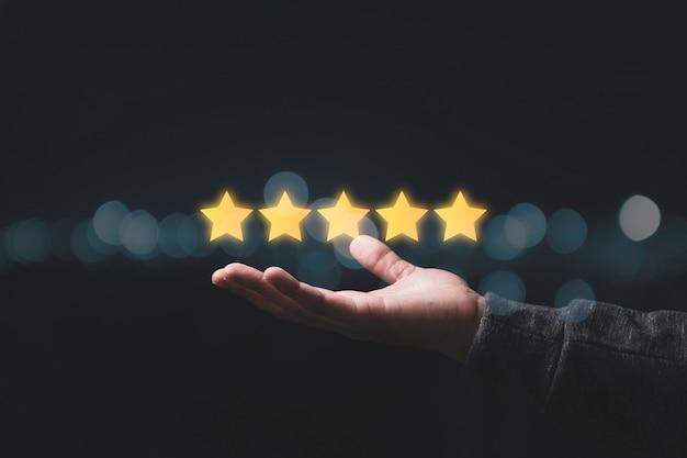 Uomo d'affari che mostra cinque stelle a portata di mano per il risultato della valutazione del cliente.