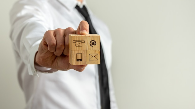 Uomo d'affari che mostra quattro cubi di legno con icone di contatto e comunicazione verso la telecamera.