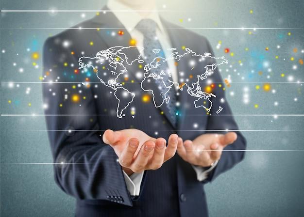Uomo d'affari che mostra la mappa del mondo digitale incandescente sullo sfondo