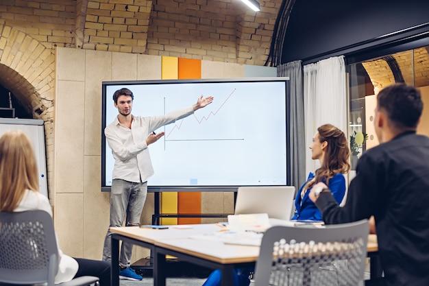 Imprenditore che mostra il grafico di crescita ai colleghi
