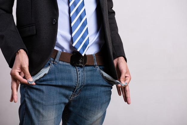 Uomo d'affari che mostra le sue tasche vuote. difficoltà finanziarie, nessun concetto di denaro.