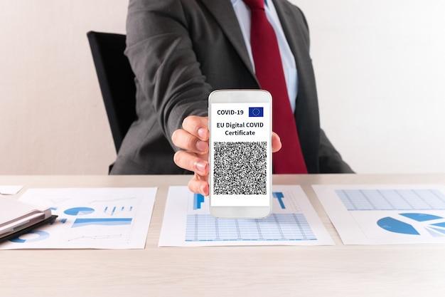 Uomo d'affari che mostra il suo certificato europeo di vaccino contro il covid