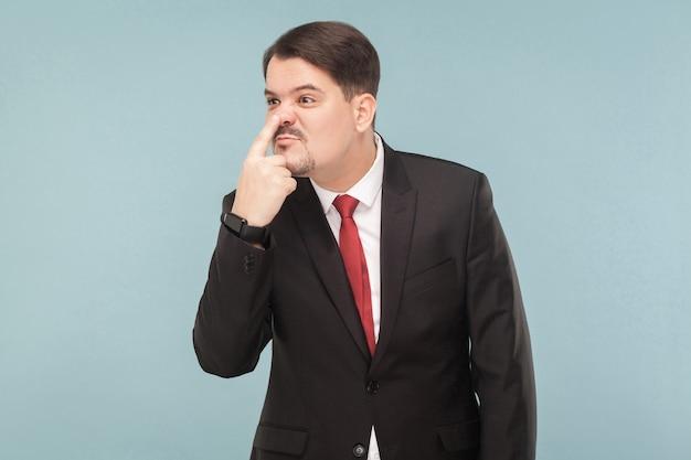 Uomo d'affari che mostra il segno del bugiardo che punta il dito in faccia
