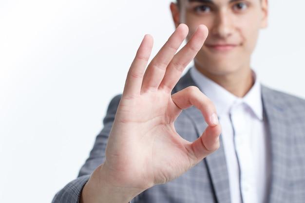 Uomo d'affari che mostra ok o mano segno pollice in su