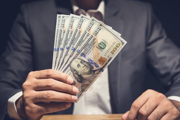 Uomo d'affari che mostra le banconote in dollari americani alla tavola nello scuro