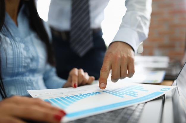L'uomo d'affari mostra la prestazione di affari sul primo piano del grafico