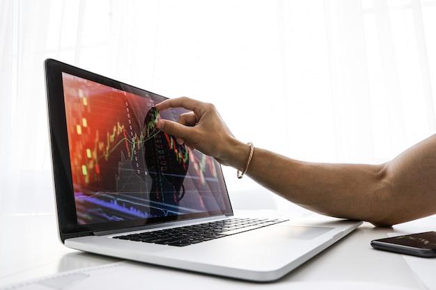 L'uomo d'affari mostra allo schermo sul computer portatile il grafico della crescita