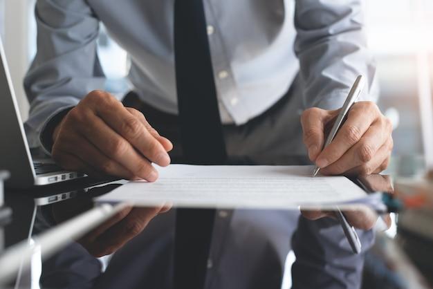 Uomo d'affari che firma un documento di contratto commerciale in ufficio