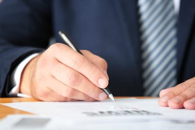 Imprenditore firma documenti in ufficio, primo piano
