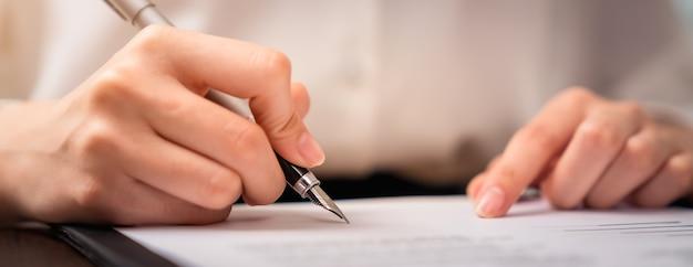 Imprenditore firma contratto finanziario e mano che tiene la penna mettendo la firma dopo aver raggiunto un accordo.