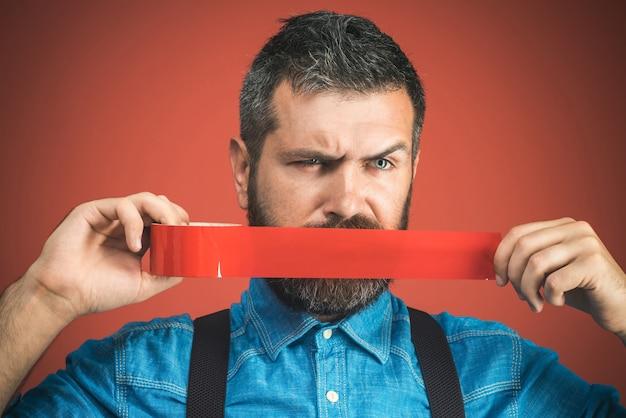 Uomo d'affari messo a tacere con del nastro adesivo sulla bocca. uomo barbuto con nastro adesivo avvolgente intorno alla bocca. l'uomo infelice in camicia di jeans ha coperto la bocca con nastro isolante rosso. isolato su sfondo rosso.