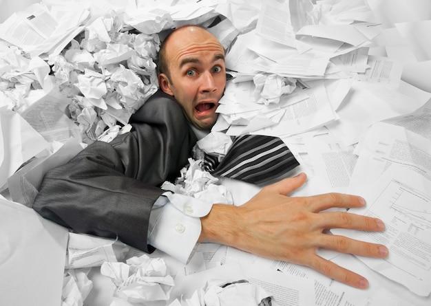 Uomo d'affari che affonda nel mucchio di documenti