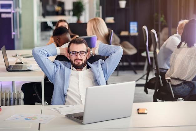 L'uomo d'affari si siede nel luogo di lavoro nell'ufficio accogliente moderno che esamina lo schermo del computer portatile si sente soddisfatto fiero con lavoro fatto, giovane che riposa mettendo le mani dietro la sua testa. nessun concetto di stress.