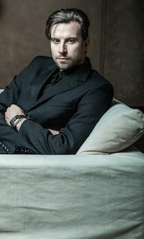 Uomo d'affari seduto su una poltrona. uomo di moda.