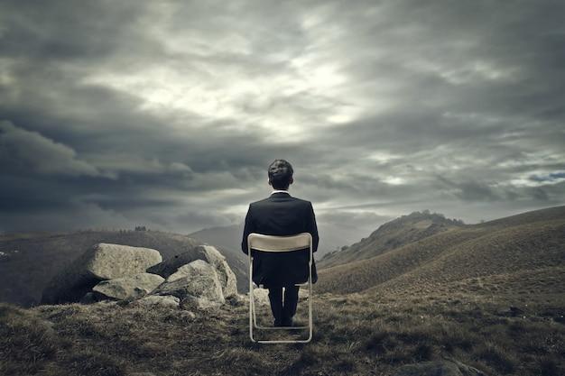 Uomo d'affari che si siede su una sedia sulla montagna