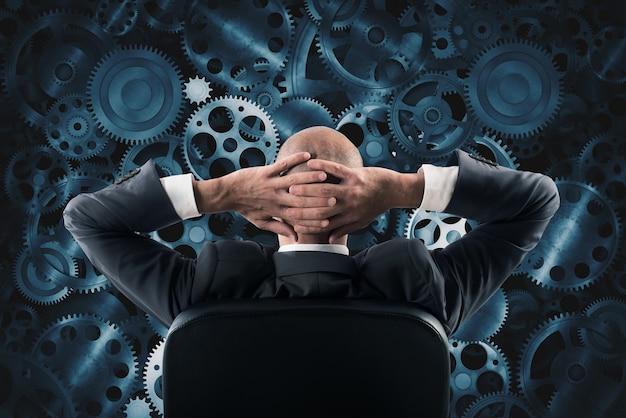 Uomo d'affari seduto su una sedia a guardare e analizzare una parete dei meccanismi di ingranaggio