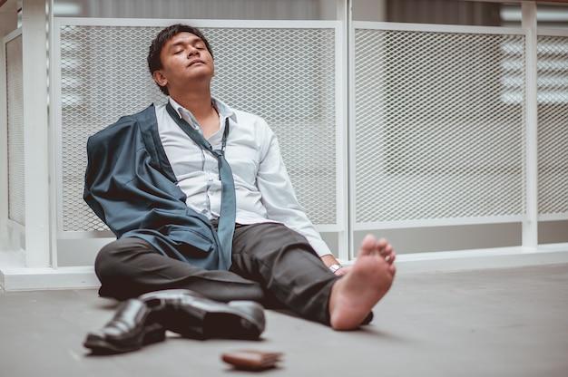 Uomo d'affari seduto sul pavimento dopo il fallimento e il licenziamento uomo disoccupato dall'azienda seduto triste
