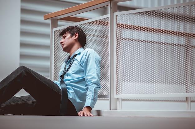 Uomo d'affari seduto sul pavimento dopo il fallimento e il licenziamento uomo disoccupato dall'azienda