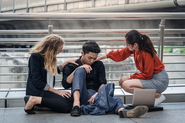 Uomo d'affari seduto sul pavimento mentre i suoi amici lo supportano