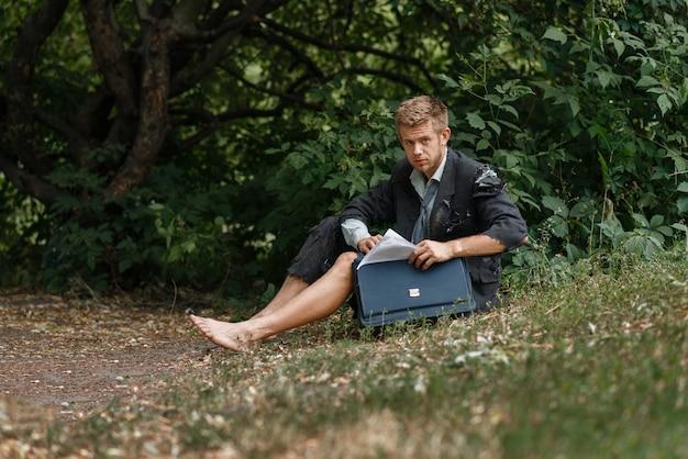 Uomo d'affari seduto per terra su un'isola deserta