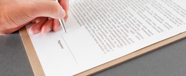 Imprenditore seduto alla scrivania in ufficio a firmare un contratto con focus superficiale sulla firma.