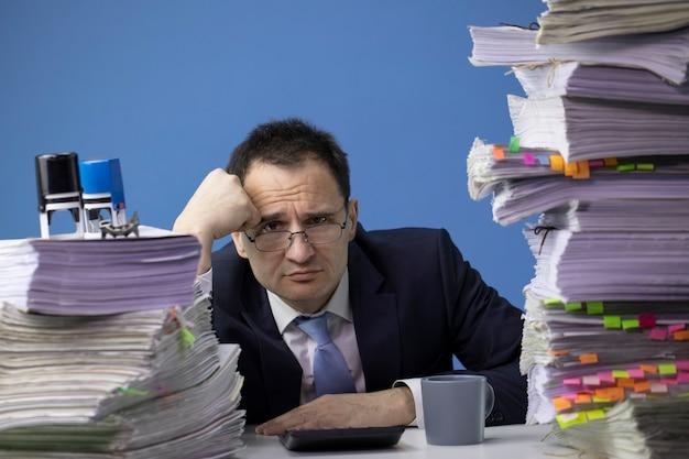 Uomo d'affari seduto alla scrivania in ufficio con un'enorme pila di documenti che sembrano tristi e depressi