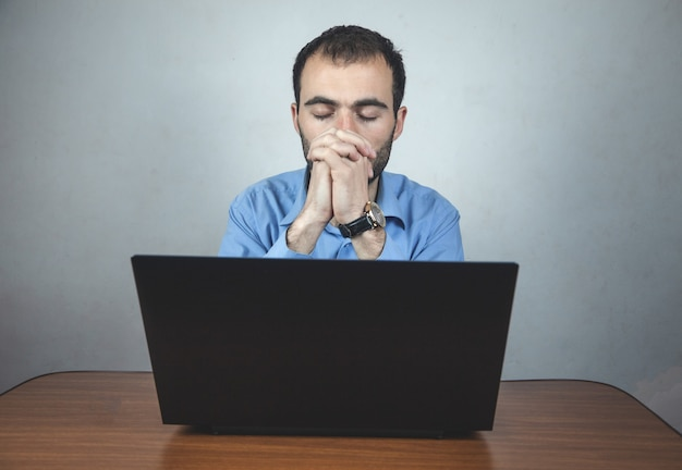 Imprenditore seduto in ufficio a pregare.