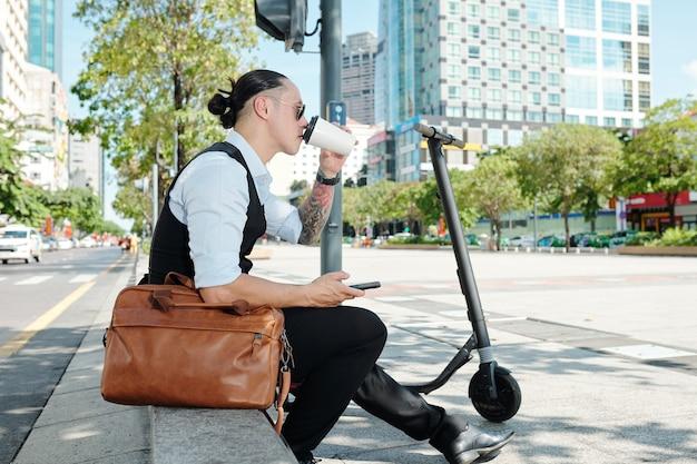 Uomo d'affari seduto sul parapetto accanto al suo scooter e godendo di gustosi piatti freschi da asporto