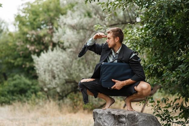 Uomo d'affari seduto sulla pietra, isola perduta