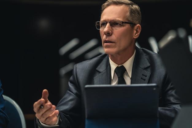 L'uomo d'affari seduto al tavolo durante una conferenza d'affari