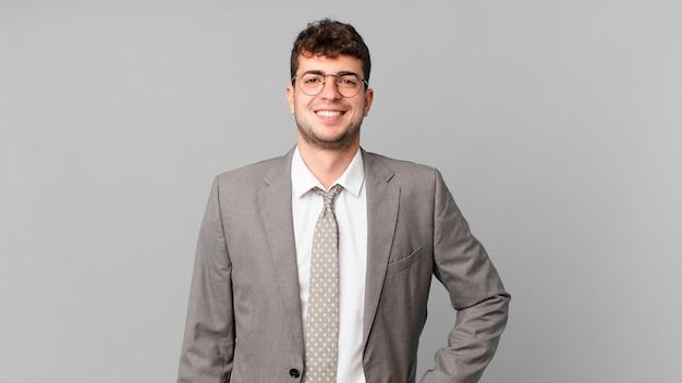 Uomo d'affari che sorride felicemente con una mano sull'anca e un atteggiamento fiducioso, positivo, orgoglioso e amichevole