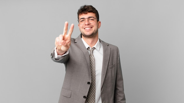 Uomo d'affari che sorride e sembra felice, spensierato e positivo, gesticolando vittoria o pace con una mano