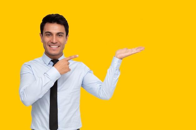 Uomo d'affari che sorride e che indica lo spazio vuoto della copia isolato su fondo giallo