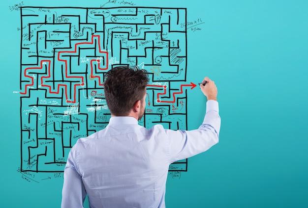 L'uomo d'affari risolve un labirinto complesso con molte difficoltà
