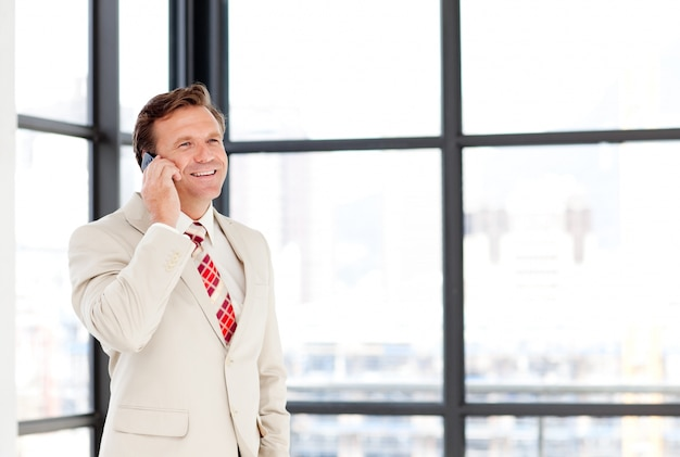 Uomo d'affari che parla su un telefono cellulare con copia-spazio