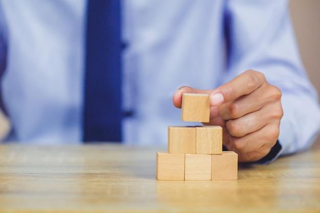 Uomo d'affari che impila i blocchi di legno nei passaggi. concetto di successo della crescita aziendale