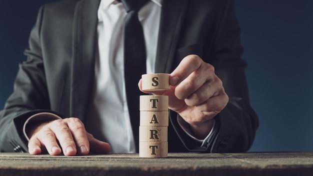 Uomo d'affari che impila cerchi in legno tagliati per assemblare la parola start in un'immagine concettuale.
