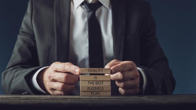 Uomo d'affari che impila pioli di legno per assemblare una qualità è il miglior segno del piano aziendale.