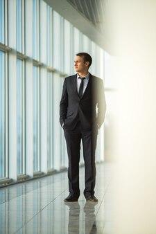L'uomo d'affari sta vicino alla finestra panoramica