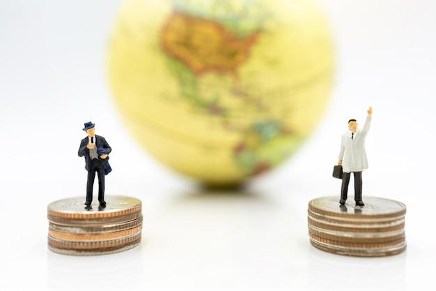 Uomo d'affari in piedi sulla pila di monete con il globo