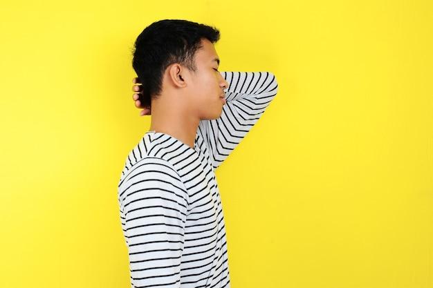 Uomo d'affari in piedi e facendo un gesto di sonno. ritratto di giovane uomo d'affari asiatico in piedi e facendo un gesto di sonno, isolato su sfondo giallo