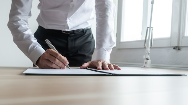 Uomo d'affari in piedi alla sua scrivania appoggiato a firmare un documento legale o scartoffie con la penna stilografica.