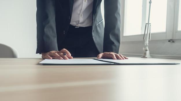 Uomo d'affari in piedi alla sua scrivania in ufficio che si appoggia a firmare un documento legale o un contratto con una penna stilografica, immagine dai toni retrò.