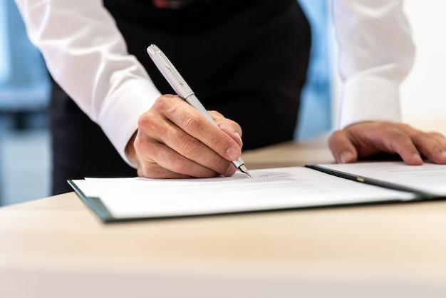 Uomo d'affari in piedi alla scrivania dell'ufficio che firma un rapporto o un contratto con una penna a inchiostro.
