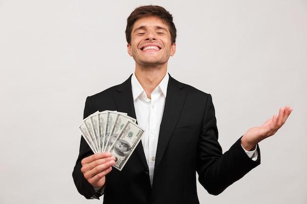 Uomo d'affari in piedi isolato tenendo i soldi.