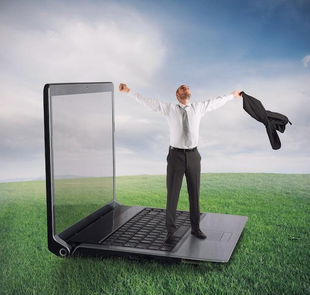 Uomo d'affari in piedi su un computer portatile